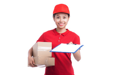 Beautiful young delivery woman in red t-shirt and cap smiling, holding a folder and making notes, on white background