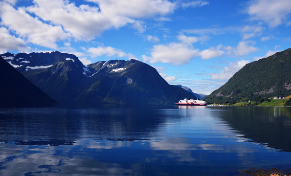 Hjorundfjord, Norway, September 2nd, 2017: Hurtigruten Cruise Ship in Fjord on a beautiful summer day