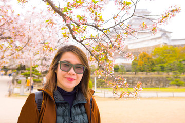 Asian short hair lady look at camera with Himeji castle in background with cherry blossom.
