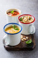 Assorted delicious homemade soups in enamel mugs with ingredients. Healthy food concept.