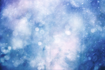 Beautiful abstract snowfall or rainfall background with raindrops and snowflakes. Blue color tone used.