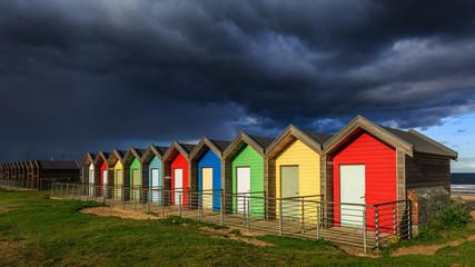Threatening sky above Blyth beach huts, Northumberland, England