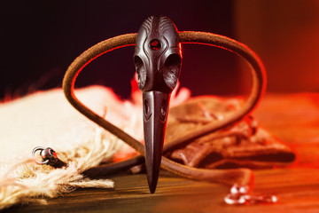 Closeup wooden raven skull as a magic amulet for witchcraft at red light background.