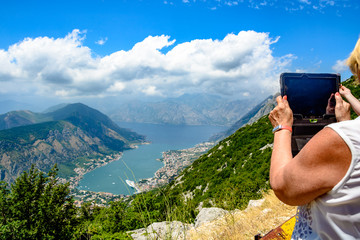 Woman taking pictures on a tablet mountain landscape