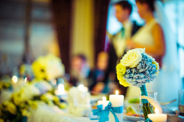 Bouquet of roses and blue hydrangeas stands on dinner table
