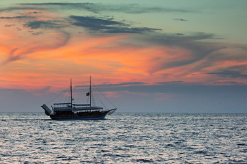 Ship sailing against colorful sky after sunset over the sea