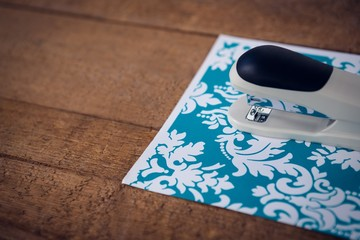 Close up of stapler on patterned paper