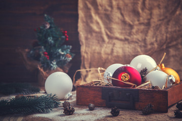 Vintage wooden box with Christmas Toys, Decorations. Holiday Postcard. Balls,Tree,Cones on aged Background.Toned image.Vintage style. selective focus.