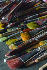 Stack of used paintbrushes. Vertical close up image.