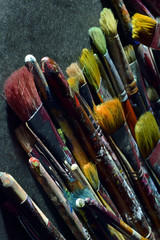 Stack of used paintbrushes on black surface. Vertical close up image.