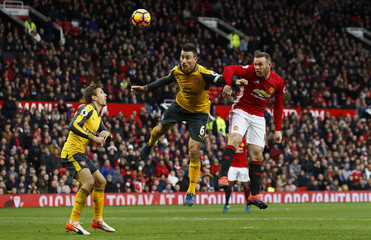 Manchester United's Wayne Rooney in action with Arsenal's Laurent Koscielny