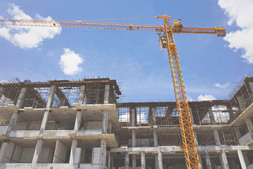 Construction site with crane and building blue sky background.