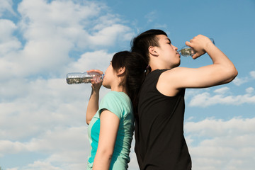 Asian couple man and woman drinking water from bottle after fitness sport exercise.