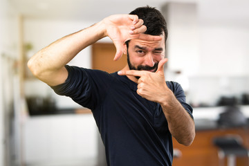 Handsome man with beard focusing with his fingers inside house