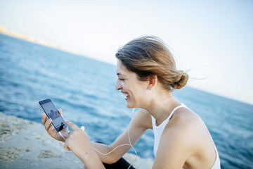 Young woman looking at photos on smartphone at the sea