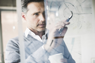 Portrait of architect checking construction plan on glass pane in office