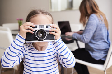 Little girl taking picture with camera while her mother working on laptop in the background
