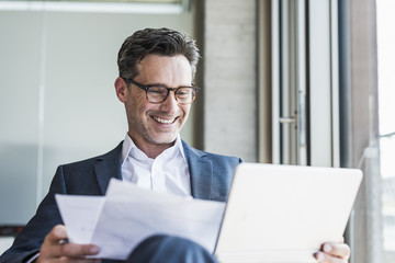 Portrait of laughing businessman with documents looking at tablet