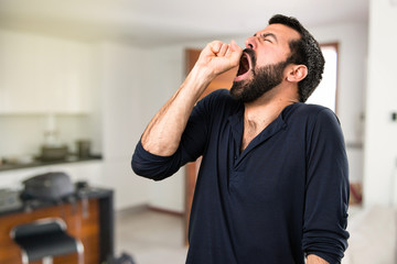 Handsome man with beard yawning inside house