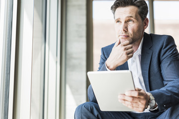 Portrait of pensive businessman with tablet looking through window