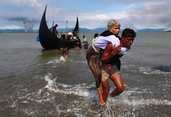 Smoke is seen on Myanmar's side of border as an old Rohingya refugee woman is carried after crossing the Bangladesh-Myanmar border by boat through the Bay of Bengal in Shah Porir Dwip