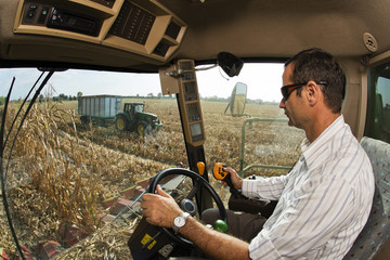 Driver of the combine, observes from the driving position, the tractor with the trailer on the field of corn threshed