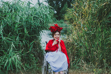 Summer conceptual portrait of beautiful young caucasian woman with red lips, red flowers in hair, sitting in wheel chair. frame with leaves wall on background.