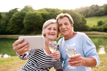 Senior couple at the lake having a picnic taking selfie