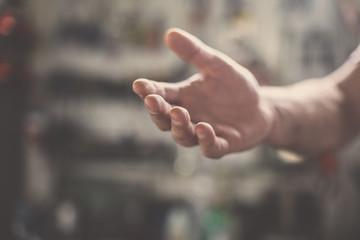 Senior worker provides hand. Close up.
