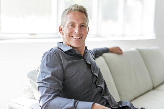 Portrait of single 40s man sitting in sofa