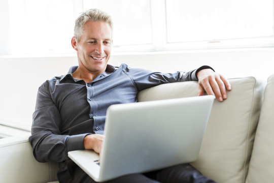 Portrait of happy mature man using laptop lying on sofa in house