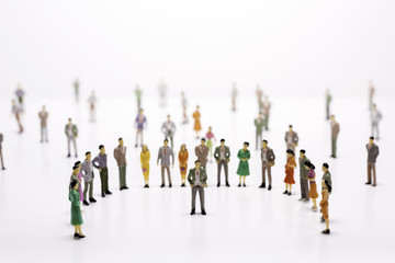Group of miniature people over white background standing in line or circle.