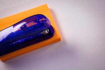 Close-up of stapler on sticky note