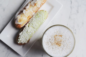 Latte and eclairs on marble background, table top view