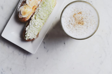 Latte and delicious eclairs with copy space on marble background