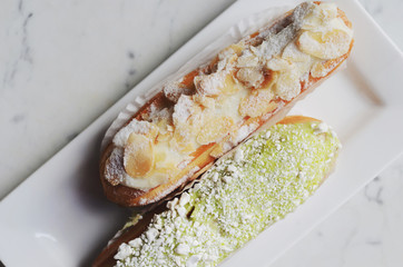 Pistachio and vanilla eclair decorated with almond on white plate