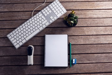 Keyboard, diary, pot plant, stationery and stapler on wooden