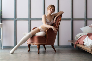 girl in white lingerie and white leggings sit in a chair