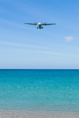 Airplane landing above beautiful beach and sea background