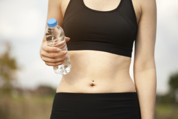 Closeup young fit woman holding water bottle