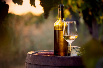 Glass of white wine and bottle with food at sunset