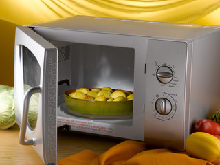pan of baked potatoes into microwave oven