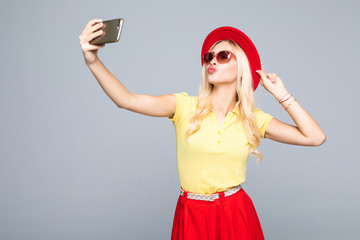 Trendy beautiful hipster girl taking selfie with mobile phone agains gray