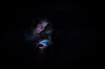 Ótimo conceito de interatividade pelas mídias sociais usando o smartphone, mulher usando o smartphone de noite na cama, retrato em low key, fundo preto, luz baixa. Imagem colorida.