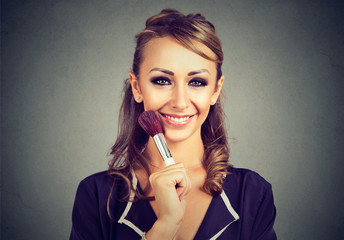 Woman with makeup, holding makeup brush in hand