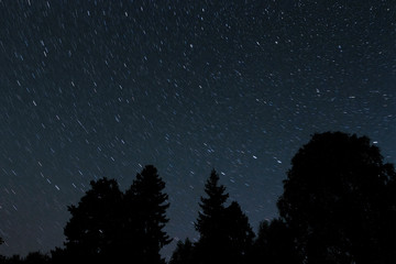 Star tracks in the night black sky around the polar star