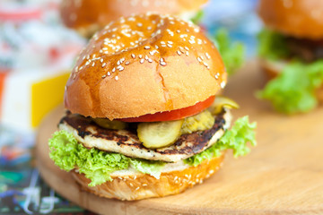 Delicious and juicy burger with salad lettuce and pickled cucumber
