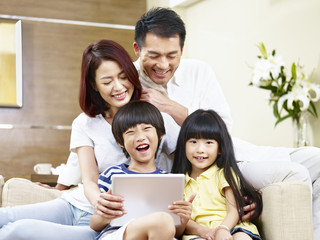 happy asian family using digital tablet together