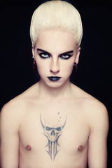 Young handsome glamorous tattooed blond man with fancy hairstyle and gothic make-up