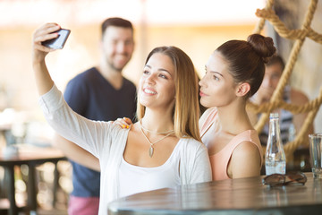 Two beautiful young women taking selfie at bar